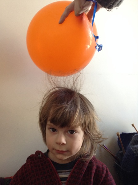 Oscar getting staticked with a balloon