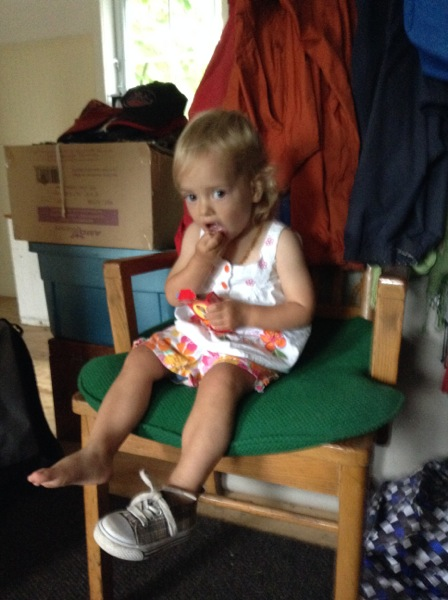 Viv in a chair with one shoe and raisins
