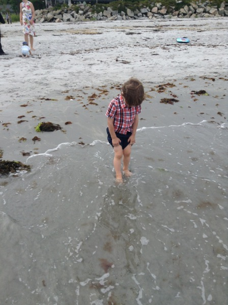 Oscar with his feet in the ocean