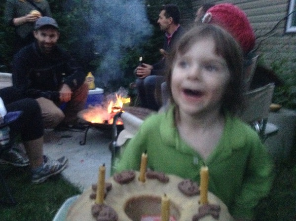 Oscar with a birthday cake standing in front of a Turkish grill with cousin Adam in the background
