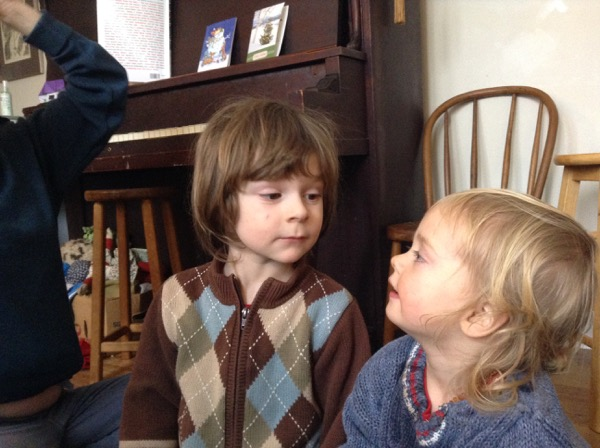 Oscar and Vivien looking at each other with the piano and a grownup in the background.