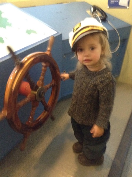 Viv at a ship's wheel in a captain's hat.