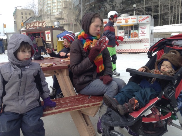 Oscar, Elizabeth and Viv at a picnic table on the ice, eating Beaver Tails.