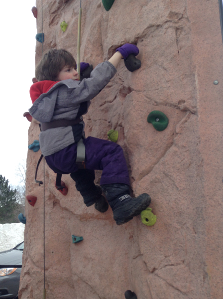 Oscar on an outdoor portable climbing wall