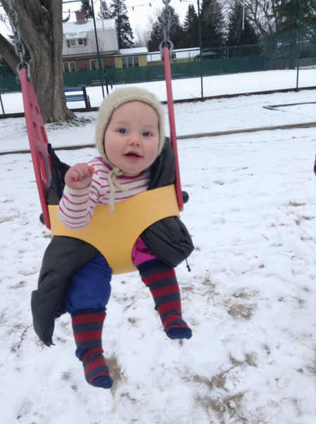 Ada on a swing in a snowy park