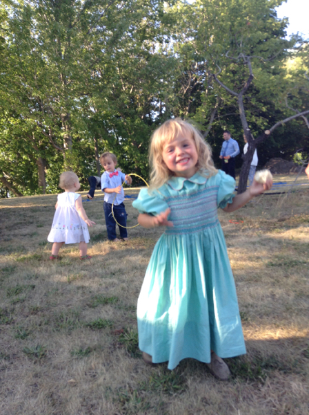 Vivien in a blue dress dancing with other kids in the background.