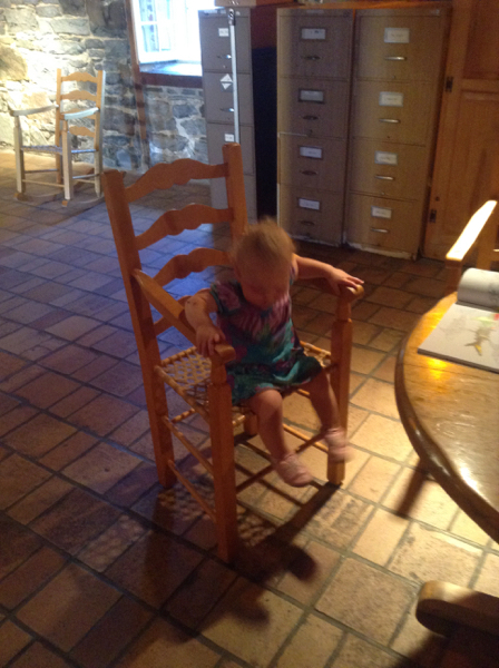 Ada in a stone-walled basement with file cabinets in the background, on a chair.