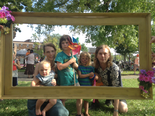 Us in a big photo frame, with Oscar holding a pinwheel and Vivien in cat face paint.