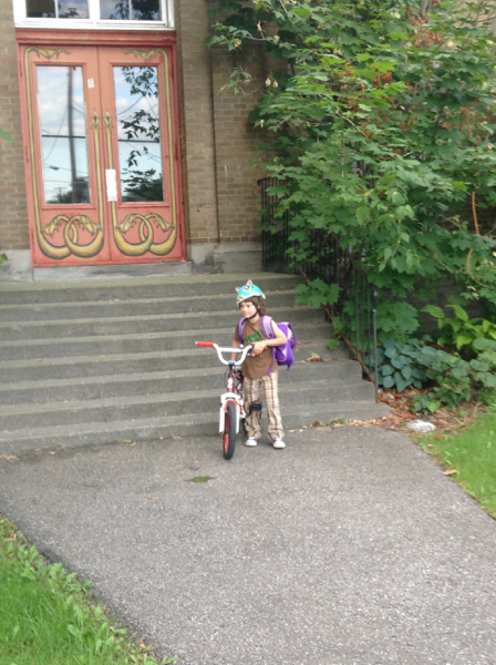 Oscar in front of the school steps, with backpack, bike and helmet.