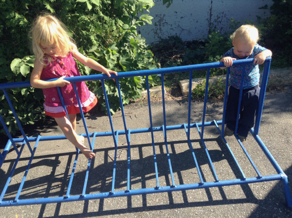 Vivien and Ada climbing a blue bike rack.