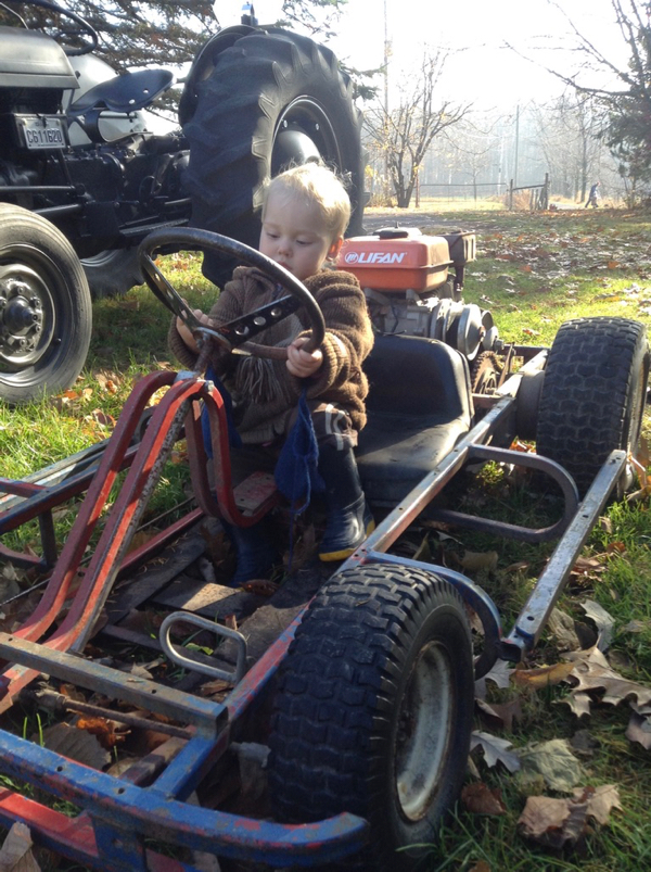 Ada in a go-kart in front of an old Ferguson tractor.