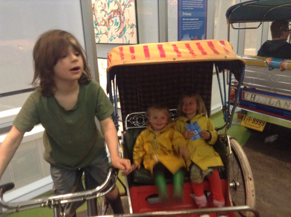 Oscar pretending to drive a bicycle rickshaw with Vivien and Ada in the passenger compartment.