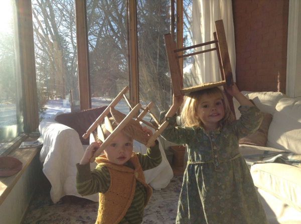 Ada and Vivien with child-sized chairs on their heads.