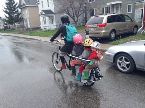Elizabeth with all three kids driving down the street on an Xtracycle.