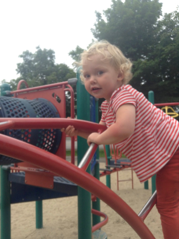 Ada climbing a twisty red ladder at the playground.
