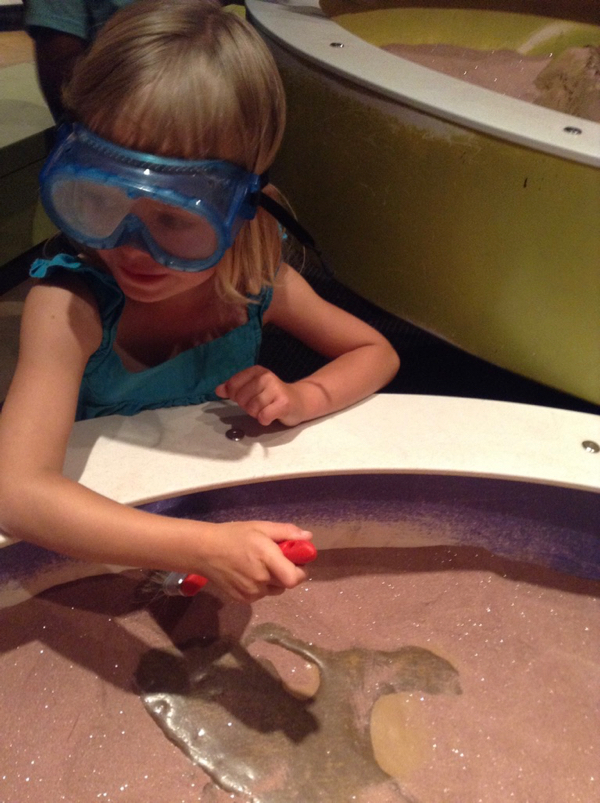 Viv with goggles and a brush, uncovering a practice fossil.