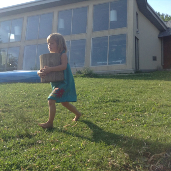 Vivien running on the lawn of a building, carrying a log about the size of her torso.