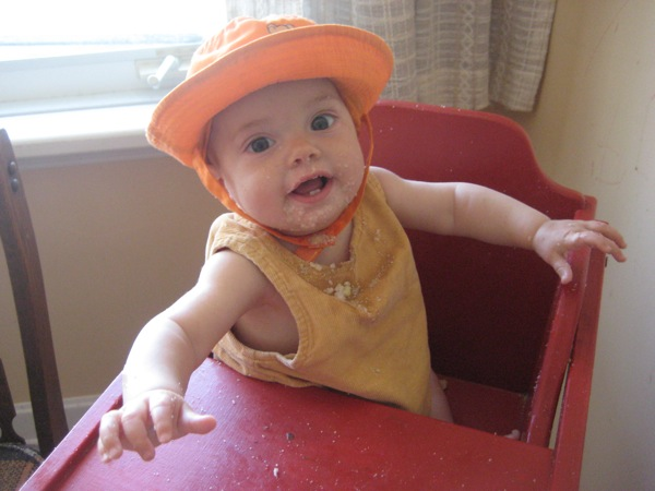 Vivien in sun hat sitting in high chair, with cream of wheat