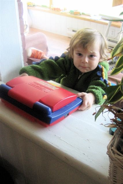 Oscar reaching for a little red laptop