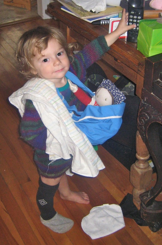 Oscar with a doll in a sling and a receiving blanket