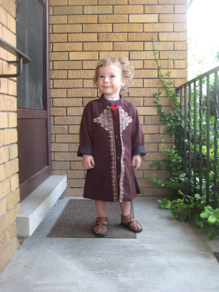 Oscar in a long brown embroidered coat and sandals, looking happy on my aunt and uncle's front porch