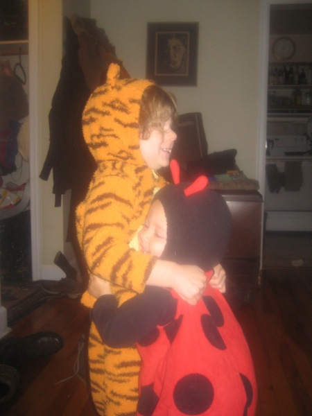 Oscar (in tiger suit) and Vivien (in ladybug suit) huggiing